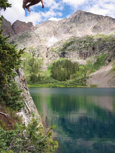 jumping into alpine lake
