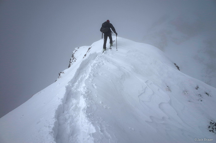 Skinning up a snowy ridge.