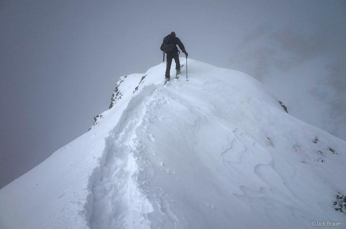 Skinning up a snowy ridge.